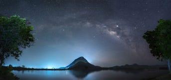 Nocne niebo z gwiazdami i drogą mleczną jest nad odbicie na wodzie i góra zdjęcie stock