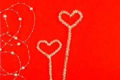 Noctilucent καρδιές με τις χάντρες σε ένα κόκκινο υπόβαθρο στοκ εικόνες