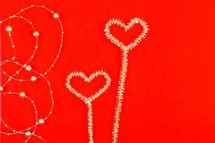 Noctilucent hearts with beads on a red background stock photo