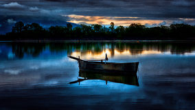 Nocturnal blue. Boat resting on lake water at sunset Royalty Free Stock Images