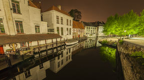 Nocturnal view of a canal in Bruges. Romantic nocturnal view of a canal in Bruges. Buildings, trees and boats are reflected in the water Stock Photos