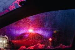 Nocy miasta światła przez przedniej szyby tła wody abstrakcjonistycznej kropli na szkło deszczu i światłach zdjęcie stock