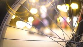 Nocy miasta życie, defocused ludzie chodzi ulicę, widok przez rowerowego koła zdjęcie wideo
