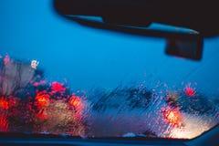 Nocy miasta droga przez przednia szyba samochodów tła wody abstrakcjonistycznej kropli na szkło deszczu i światłach zdjęcia royalty free