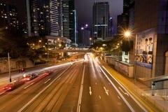 Nocy miasta ulicy z samochodu jeżdżeniem przy rozdrożem z miastowymi strukturami Zdjęcie Stock