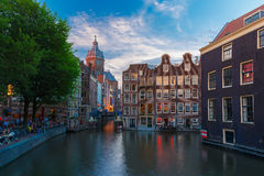 Nocy miasta widok kanał, kościół i most Amsterdam, Zdjęcie Stock