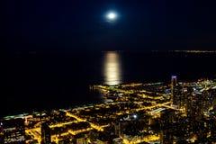 Nocy miasto zaświeca z blaskiem księżyca na jeziorze obraz royalty free