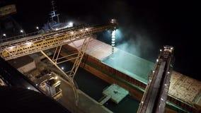 Nocy panorama ładować zbożowe uprawy na masowym freighter statku przez bagażnika otwierać ładunków chwyty przy silosowym terminal zbiory