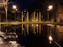 Nocy scena po tym jak deszcz - lampion zaświeca i kałuża zdjęcie stock