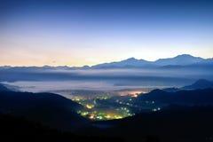 Nocy sceny wizerunek miasto mgła wśród gór i światła obraz stock