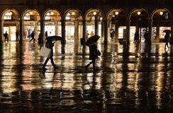Nocy sylwetka ludzie z parasolem na dżdżystej nocy w Świątobliwym Mark kwadracie w Wenecja z złotym światłem w backgr obrazy stock