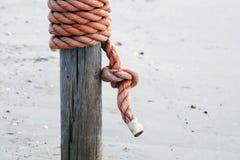 Node on the pier. Corda nautica arrotolata su un palo in spiaggia stock photography