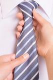 Nodo del foulard e mani femminili. Immagine Stock