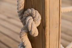 Nodo di una corda spessa su un supporto di legno immagini stock libere da diritti