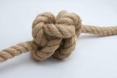 Nodo in su legato della corda isolato su una priorità bassa bianca Fotografia Stock