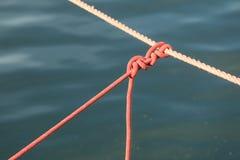 Nodo sulla linea della corda sopra l'acqua dell'oceano del mare Immagine Stock