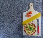 Noedel in knoflook en olie, in een kom met bacon en tomaten wordt gediend die Hoogste mening met ruimte voor tekst stock foto's