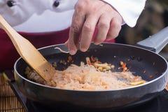 Noedel van de chef-kok stitr de gebraden rijst voor het koken van Stootkussen Thai royalty-vrije stock afbeeldingen