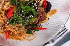 Noedels met kalfsvlees en paddestoelen Gediend op een transparante plaat met mes en vork met greens en peper stock afbeeldingen