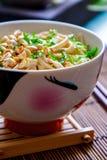 Noedels met pinda's en nootsaus in een ceramisch komclose-up stock afbeeldingen