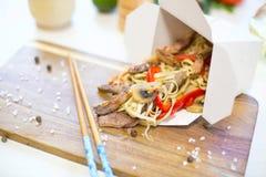 Noedels met varkensvlees en groenten in meeneemvakje op houten lijst stock afbeeldingen