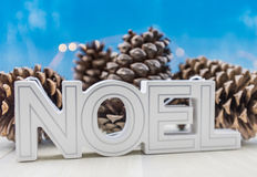 Noel Block Text Skewed with Pine Cones. On table top Royalty Free Stock Photos