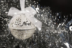 Noel Christmas Ornament. A sliver Christmas ornament engraved with the word Noel. Ornament is suspended with a white ribbon, silver tensile in background royalty free stock photos