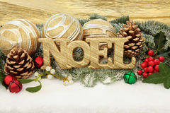 Noel. Christmas noel sign with gold bauble decorations, holly and winter greenery over snow background Stock Images