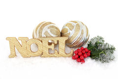 Noel Decorative Display. Noel gold glitter sign with christmas holly, fir and bauble decorations on snow over white background Royalty Free Stock Photography