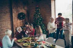 Noel morning gathering. Nice joyful cheerful grey-haired grandpa stock images