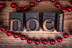 Noel printer blocks. The word NOEL written with vintage wood printer blocks. Christmas message over old wood with a string of decorative red beads Royalty Free Stock Photo
