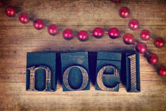 Noel printer blocks. The word NOEL written with vintage wood printer blocks. Christmas message over old wood with a string of decorative red beads Stock Image