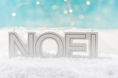 NOEL in Snow. With blue and white bokeh background Royalty Free Stock Images