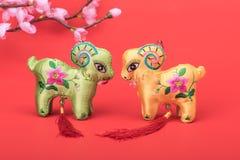 Noeud chinois de chèvre sur le fond rouge Photos stock