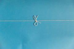 Noeud de ficelle au-dessus de carton bleu Photographie stock libre de droits