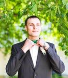 Noeud papillon de contacts des mains de l'homme sur un costume images libres de droits
