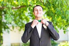 Noeud papillon de contacts des mains de l'homme sur un costume photo libre de droits