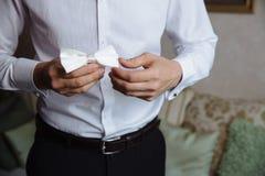 Noeud papillon de contacts des mains de l'homme sur un costume images stock