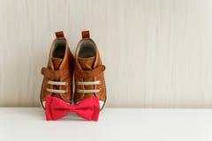 Noeud papillon et chaussures sur le mur de fond avec le papier peint Image libre de droits