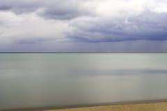 Nog de wateren van het aquamarijnmeer en zandig strand in de voorgrond o Royalty-vrije Stock Fotografie