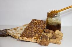 Noga met honing en pinda's op witte achtergrond Stock Afbeeldingen