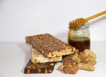 Noga met honing en pinda's op witte achtergrond Royalty-vrije Stock Afbeeldingen