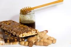 Noga met honing en pinda's op witte achtergrond Stock Fotografie