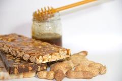 Noga met honing en pinda's op witte achtergrond Stock Afbeelding