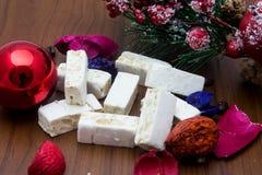 Noga, traditioneel Spaans snoepje voor Kerstmis de zoete donkere achtergrond van de amandelnoga met sneeuw en spardecoratie Stock Afbeeldingen