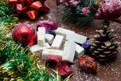 Noga, traditioneel Spaans snoepje voor Kerstmis de zoete donkere achtergrond van de amandelnoga met sneeuw en spardecoratie Stock Afbeelding