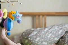 noga troch? Dziecko w rodzicach łóżkowych Kolorowe i śmieszne mobilne zabawki zdjęcie stock