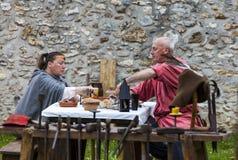Couples médiévaux prenant le déjeuner Image stock