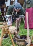 L'eau de versement d'homme médiéval Photographie stock