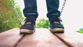 Nogi dziecka chlanie na drewnianej huśtawce w lato parku i pozycja zdjęcie wideo
